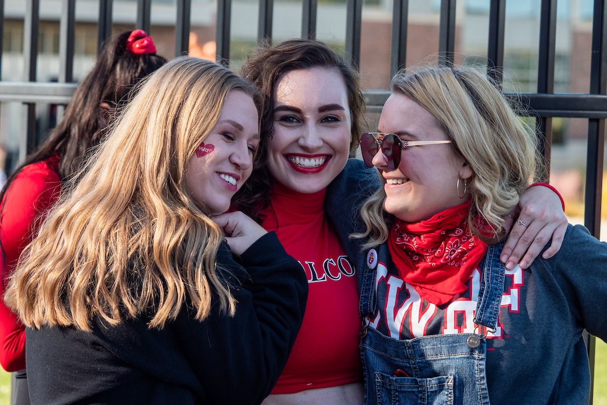 Three female students hugging and smiling at a UWRF football event. The students have Falcon and