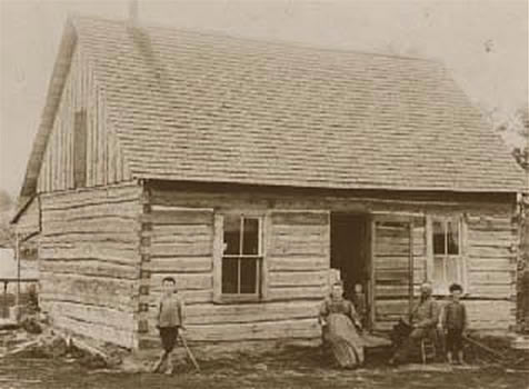 Dr. Aker and family outside their homestead cabin