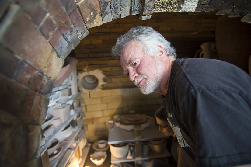 Professor Randy Johnston tends to the wood-fired kiln