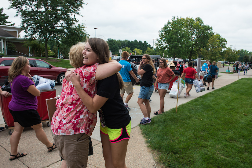 Student and parent hugging on move-in day