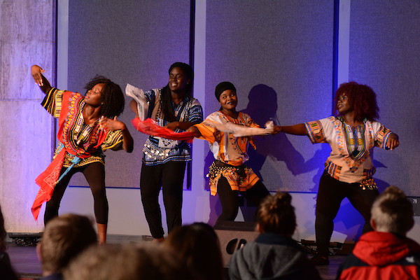 This is a picture from African night 2015. This photo was taken mid-dance performance of four students showcasing various dance styles from different countries in Africa. The students are wearing brightly colored clothing and holding bandanas.