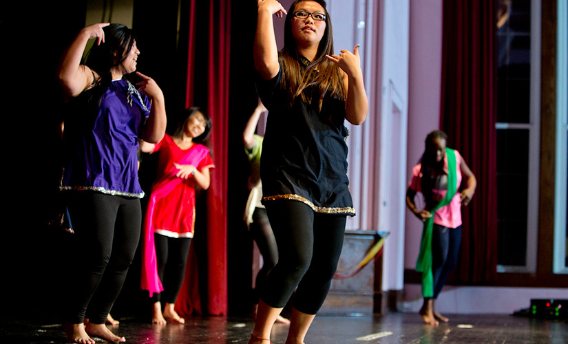 This is a photo taken mid-dance performance at Culture fest, an event put on by AASA each fall semester. The photo focuses on a student performer wearing glasses and a black ensemble while four other student performers are dancing behind them.
