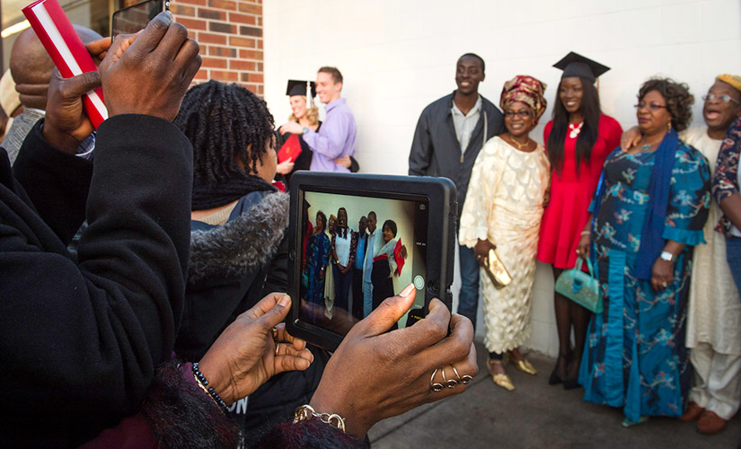 This is a photo of graduating students at Commencement taking pictures with their loved ones. The photo focuses on a pair of hands holding an iPad taking a photo of one of the students, wearing a graduation cap and red dress, and their loved ones.