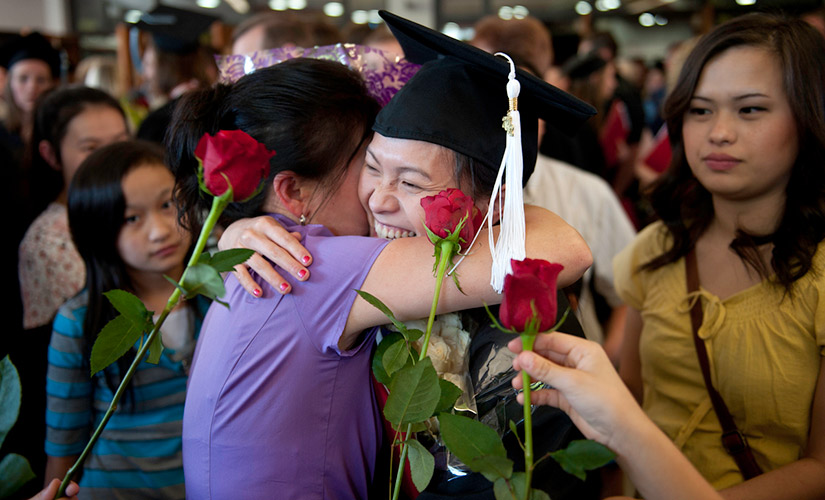 This is a photo from Commencement. A graduating student, wearing their cap and gown with a white tassel hugs a loved one after receiving their diploma. There are three red roses held up in the front of the picture.