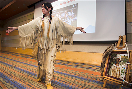 This is a photo from a previous Native American Heritage Month Celebration. The presenter is wearing their traditional attire with braided hair. They are standing with their left leg in front of their right leg and their arms extended out.