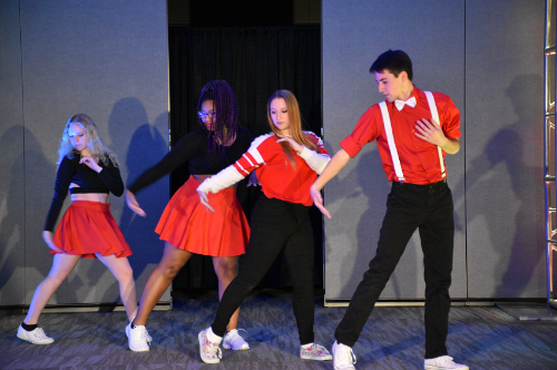 This is a photo of a performance from Falcon's Got Talent entitled Dancing with Diversity. The four students in this photo are wearing black and red outfits and have their right arm and leg extended out mid-dance move.