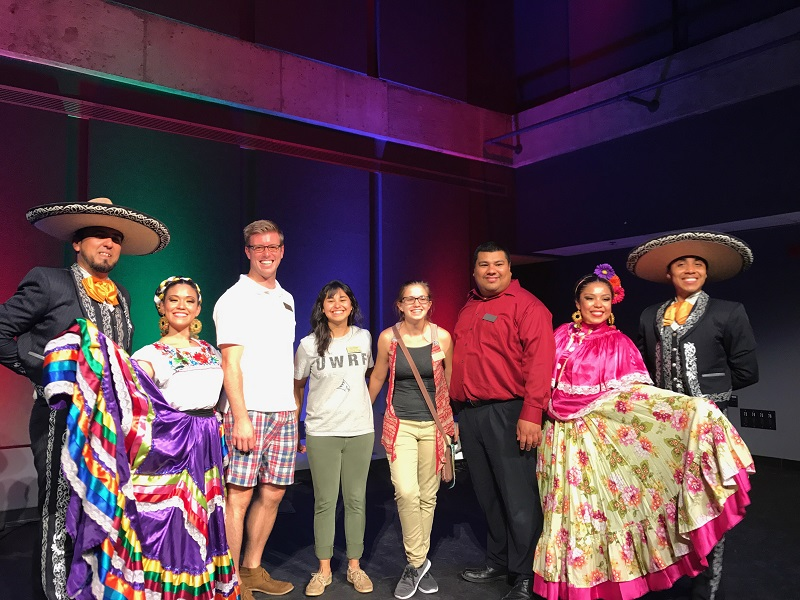 This is a photo of our four staff members and the four Ballet Folklorico Mexico Azteca performers at the Fall 2017 Mexican Independence Day Celebration event. The four performers are wearing traditional Folklorico dance attire.