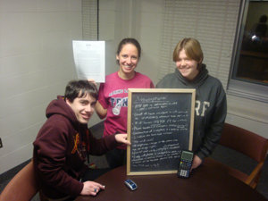 Three math students showing board with assumptions as topic