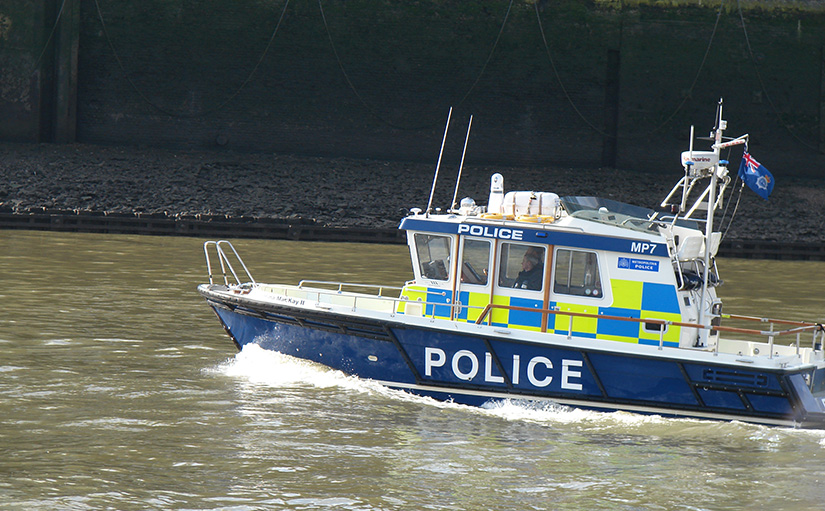 London police boat on the River Thames during low tide