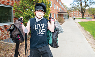 Masked student in UWRF shirt hauling around a bunch of bags