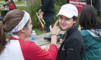 Students painting their faces at a homecoming tailgate event