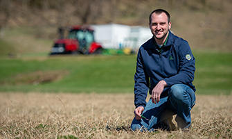 Matt Kortbein, a Crop and Soil Science Major kneeling in a field
