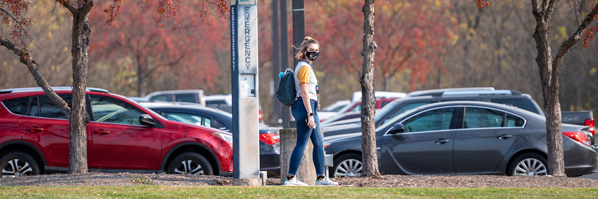 Student walking in fall campus colors