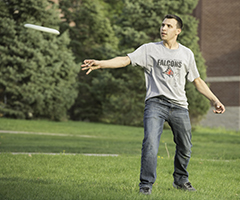Student throws a flying disc on the campus mall in spring